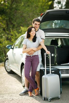 Glückliche Pärchen, mit Koffer und Auto