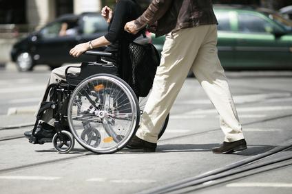 Rollstuhlfahrer wird geschoben